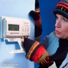 Woman cold near thermostat